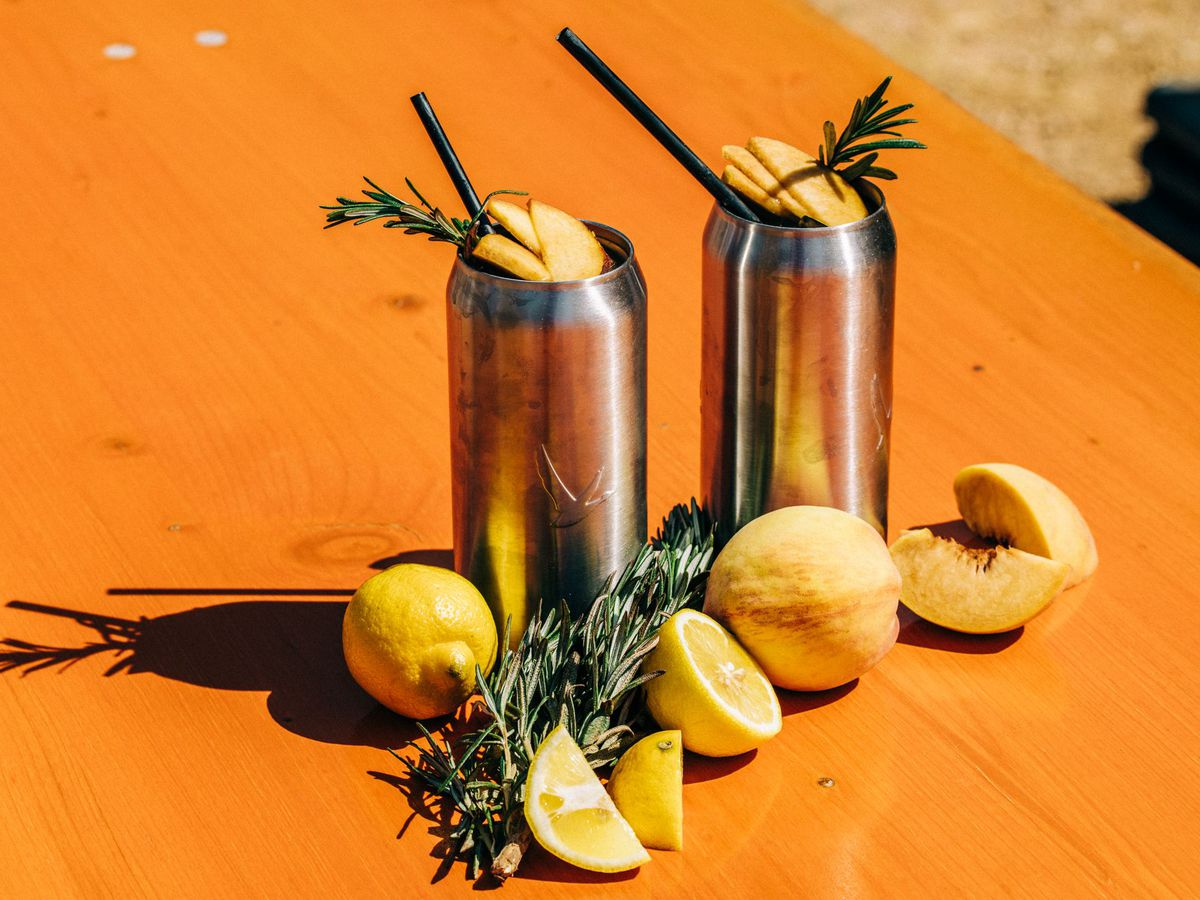 Two silver cans sit on a bright orange table surrounded by and topped by lemons, peaches and rosemary.
