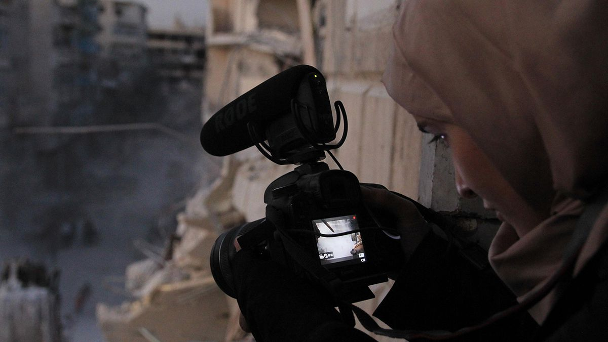 "Waad Al-Kateab in a muslim headscarf stands in front of a ruined building and looks at the image in her digital camera while shooting footage for the documentary ""For Sama."""