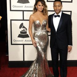 """""""Chrissy Teigen was dipped in gold in a beautiful Johanna Johnson gown. A perfect example of a star working the hell out of a dress! Loved the clean neckline, minimal jewelry, and the belted bodice. 10's across the board! John Legend dazzled in a Gucci ta"""