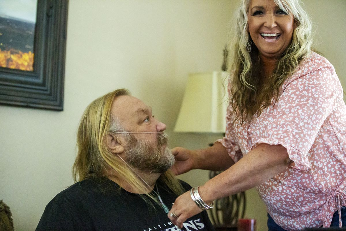 Stan Ellsworth looks up at his wife Stacey Ellsworth as she helps his with his oxygen tube as they talk about their life together and Stan's road to recovery from COVID-19 on Monday, July 6, 2020, at their home in Draper.