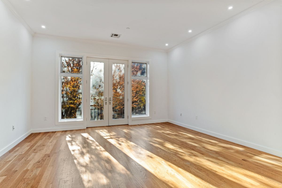 A living area with hardwood floors, white walls, and a door that leads to a balcony.