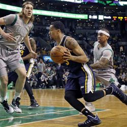 Utah Jazz guard Trey Burke (3) drives to the hoop against Boston Celtics guard Isaiah Thomas, right, and Celtics center Kelly Olynyk (41) during the first half of an NBA basketball game in Boston, Wednesday, March 4, 2015. (AP Photo/Elise Amendola)