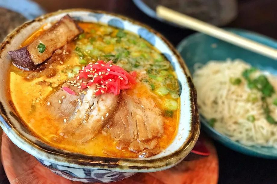 Ramen at Marufuku topped with pork, pickled ginger, and scallions in a blue and white bowl.