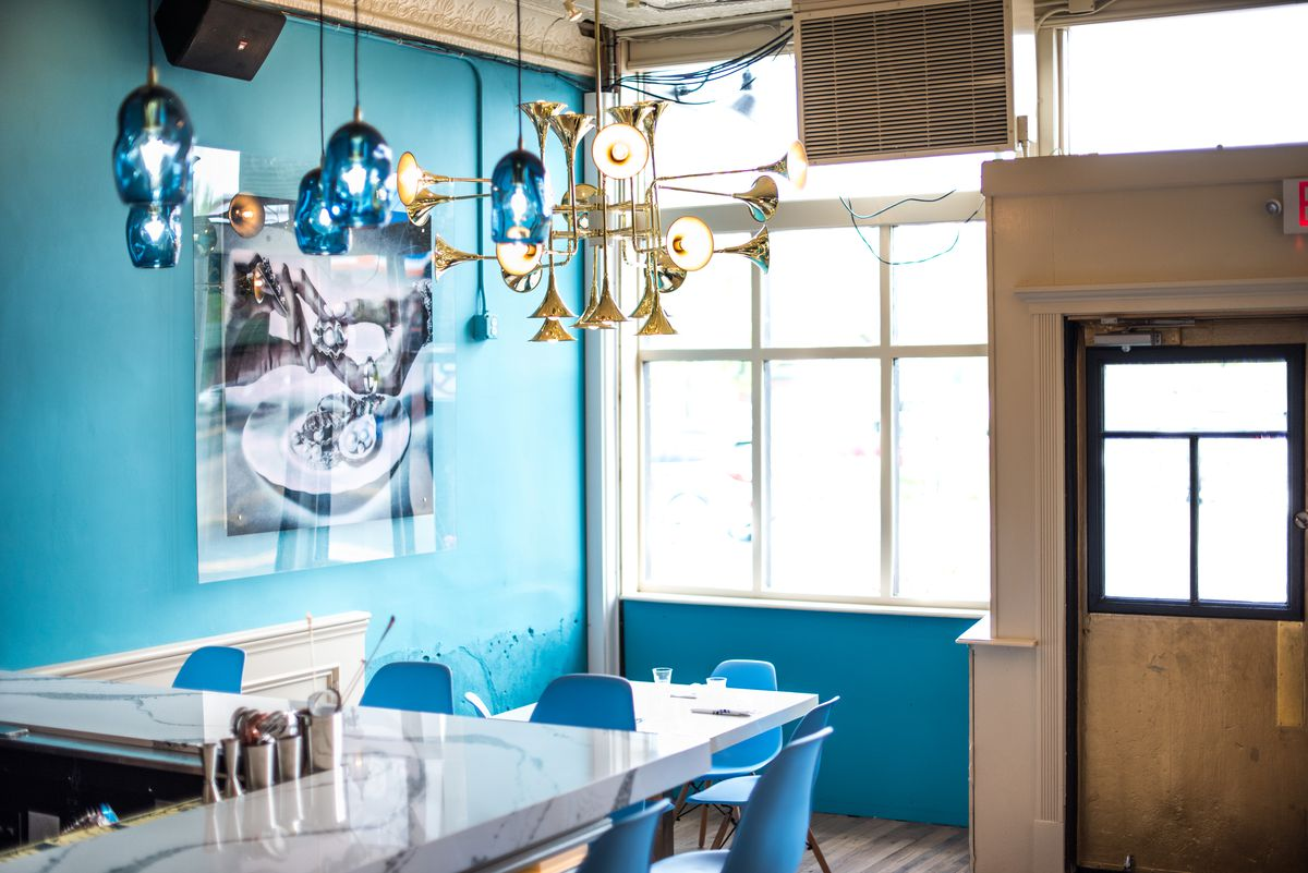 Vibrant light blue walls, white marble bar, and white table set inside the original Pearl & the Thief location
