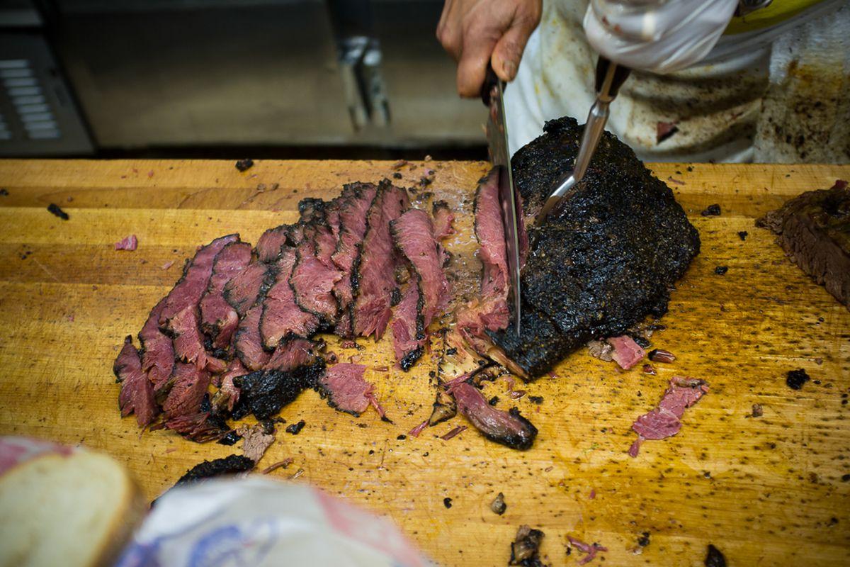 A butcher chops up pastrami on a wooden block at Katz's