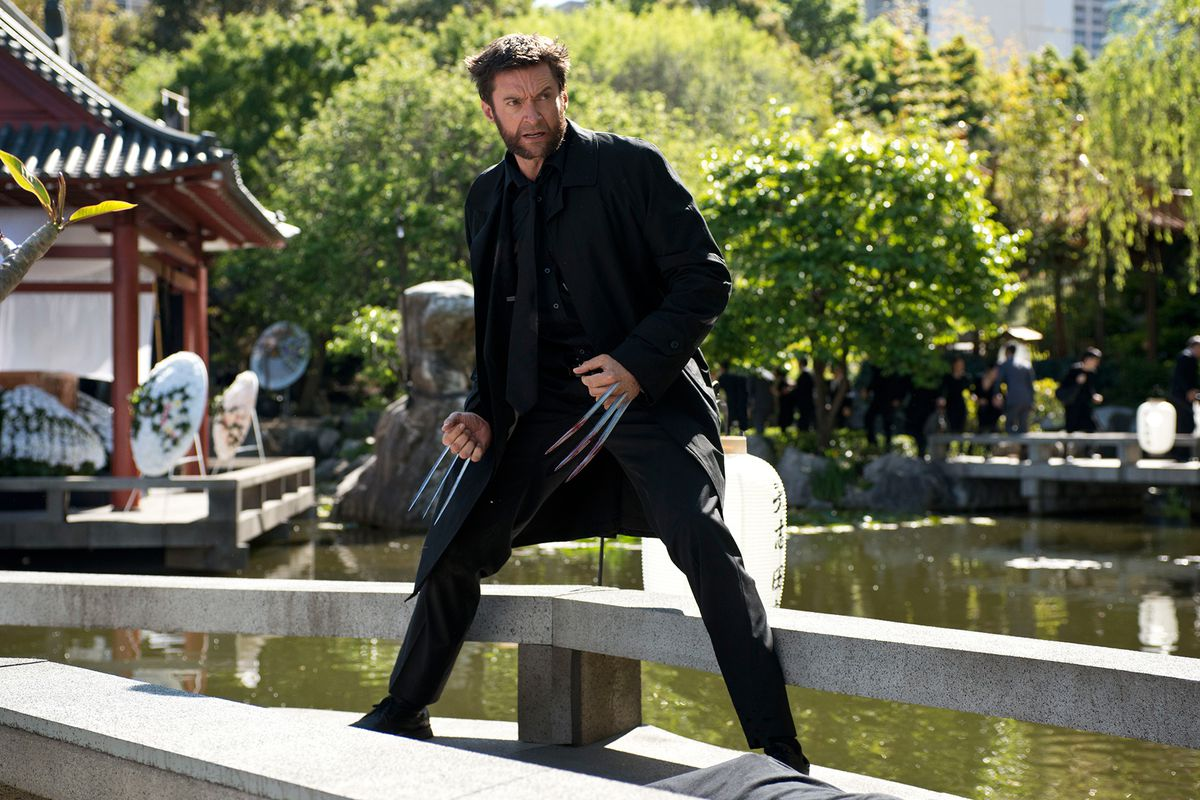 Wolverine, played by Hugh Jackman, stands on a ledge near a river. His pose is defensive — he has his claws extended and is standing ready for a fight. He is, however, wearing a nice jacket.