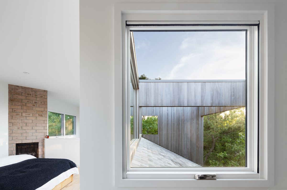 A large square window in the bedroom looks out to trees and the sky.
