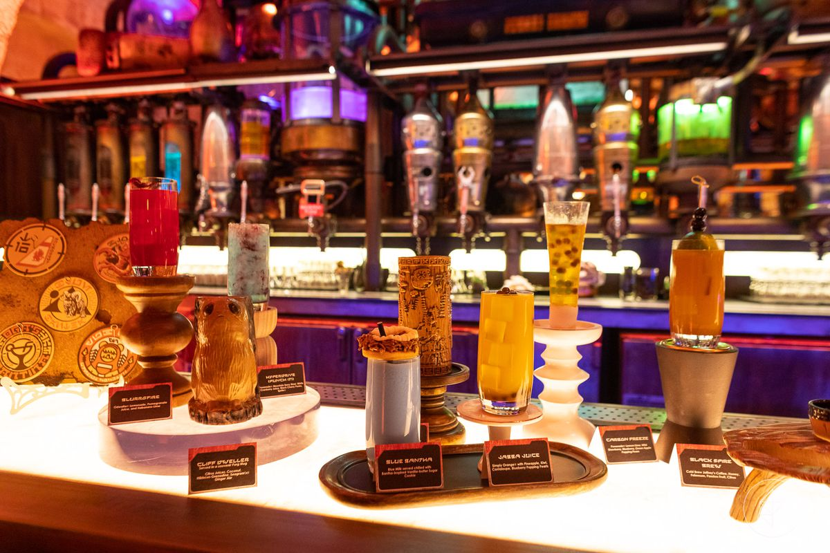 A bar at Galaxy's Edge in Disneyland. There are various drinks displayed on the bar with drink labels.