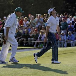 Rory McIlroy, of Northern Ireland, reacts when he sees how close his ball landed next to the cup on the 18th green during the third round of the Masters golf tournament Saturday, April 7, 2012, in Augusta, Ga. Left is caddie J.P. Fitzgerald.