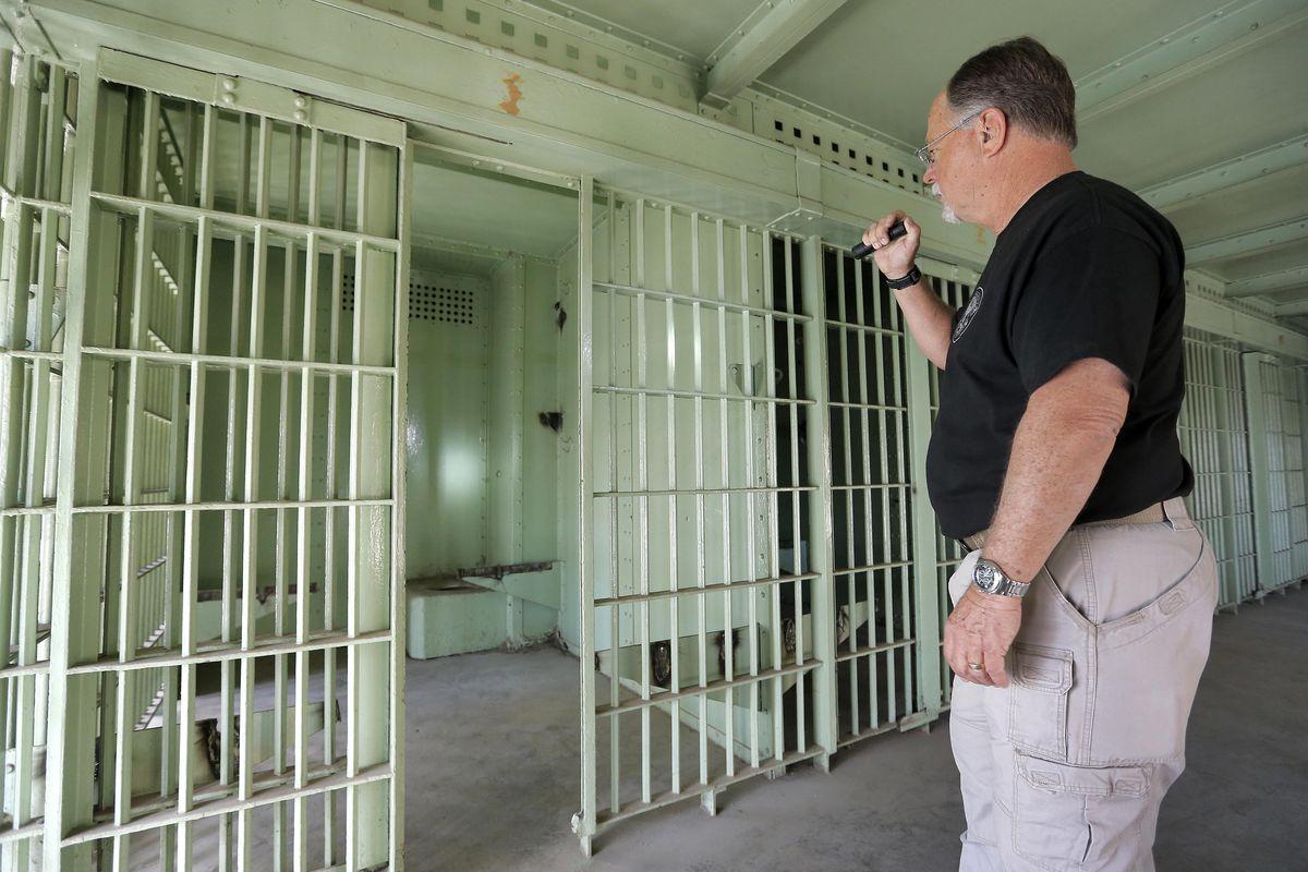 Retired Phoenix Police Sgt. Steve Proctor shines a flashlight inside the jail cell that housed Ernesto Miranda in Phoenix.