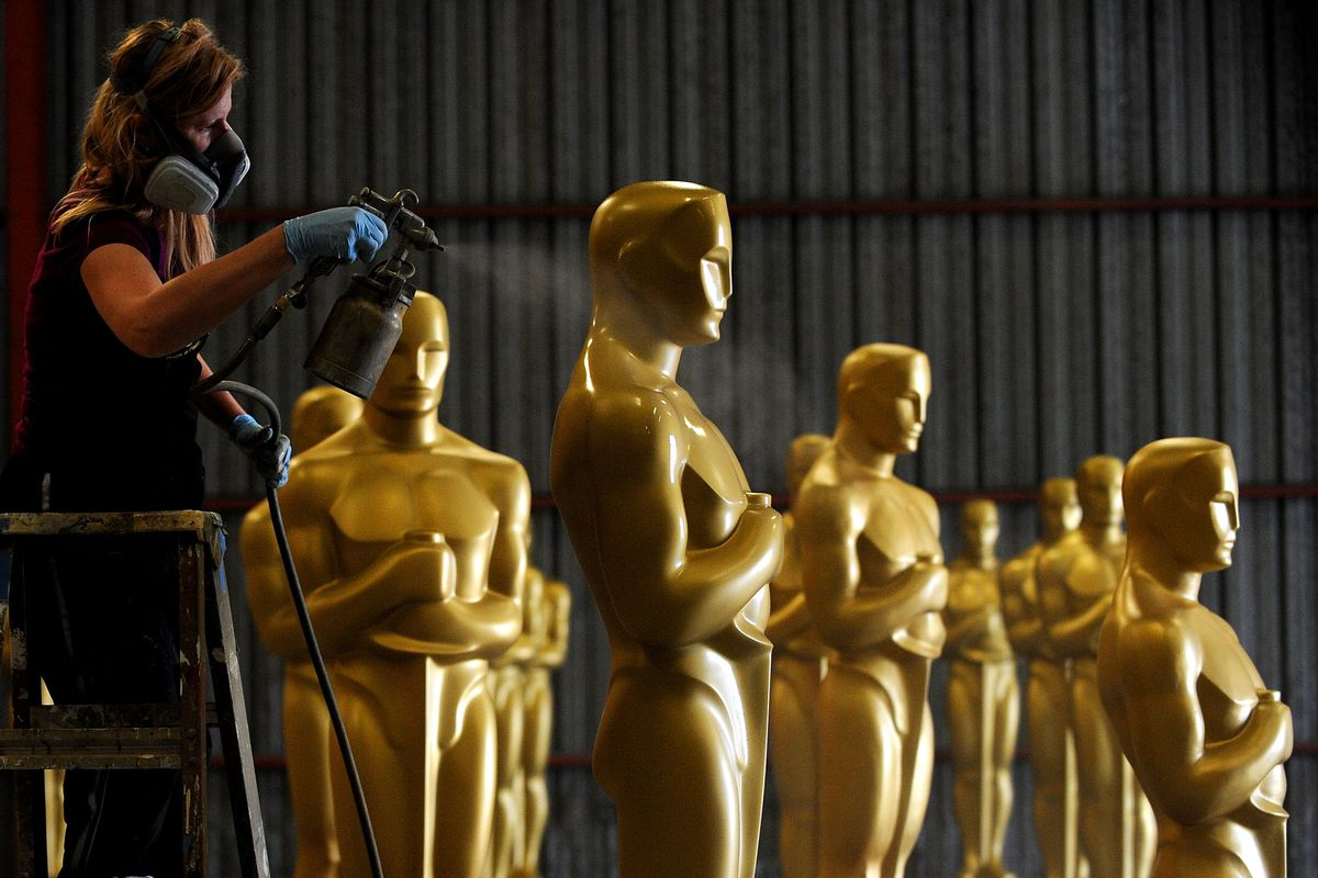 An artist wearing a breathing mask uses a paint gun to spray gold onto full-sized Oscar statues that will be used to decorate the Academy Awards event.