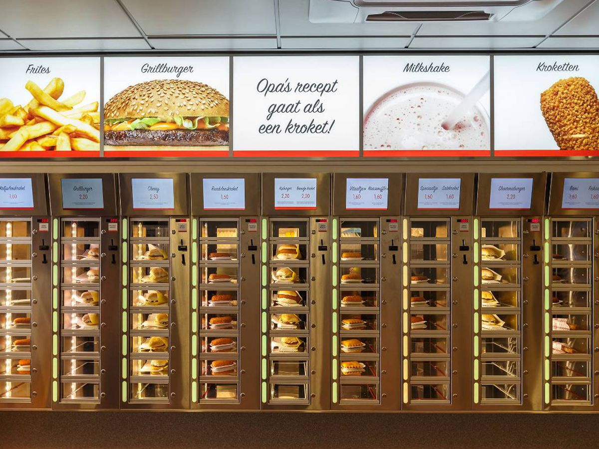 A series of compartments hold food waiting for customers to purchase automatically from the automat machine, with large images of menu items and prices listed above in back-lit signs.