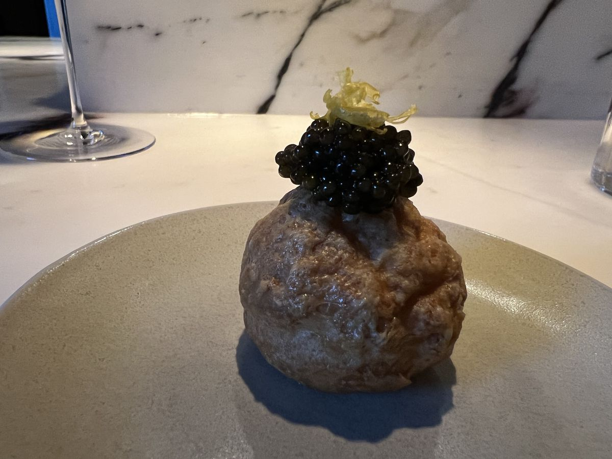 A mound of black caviar sits over a brown cheddar gougere