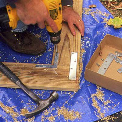 Man Assembles Frame Parts With Drill To Install Porch Lattice