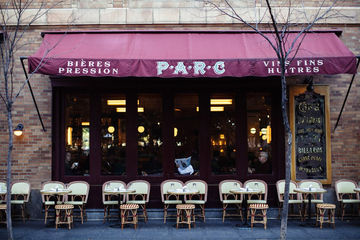 front of a restaurant with sidewalk seating and an awning that says parc