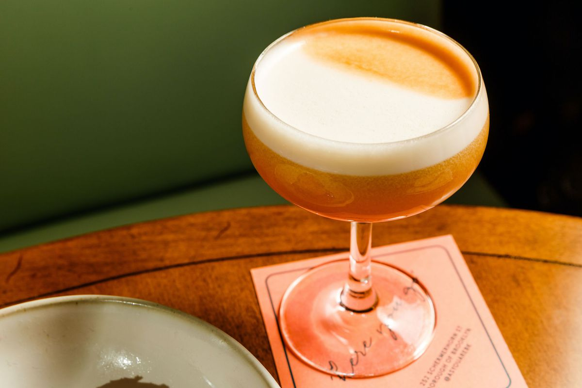 A coupe glass with an orange color liquor with a white foam on top.