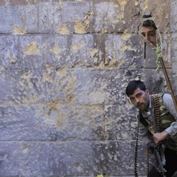 A Free Syrian Army soldier, right, looks through a mirror which helps him see Syrian troops from the other side, as he takes his position with his comrade during fighting, at the old city of Aleppo city, Syria, Monday Sept. 24, 2012. Most of those fighting the regime of President Bashar Assad are ordinary Syrians and soldiers who have defected, having become fed up with the authoritarian government, analysts say. But increasingly, foreign fighters and those adhering to an extremist Islamist ideology are turning up on the front lines.
