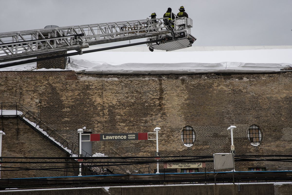 Chicago Fire Department firefighters spray water on the roof of the Aragon Ballroom to knock loose at least a foot snow that had accumulated and damaged a brick wall on the North Side building Tuesday.