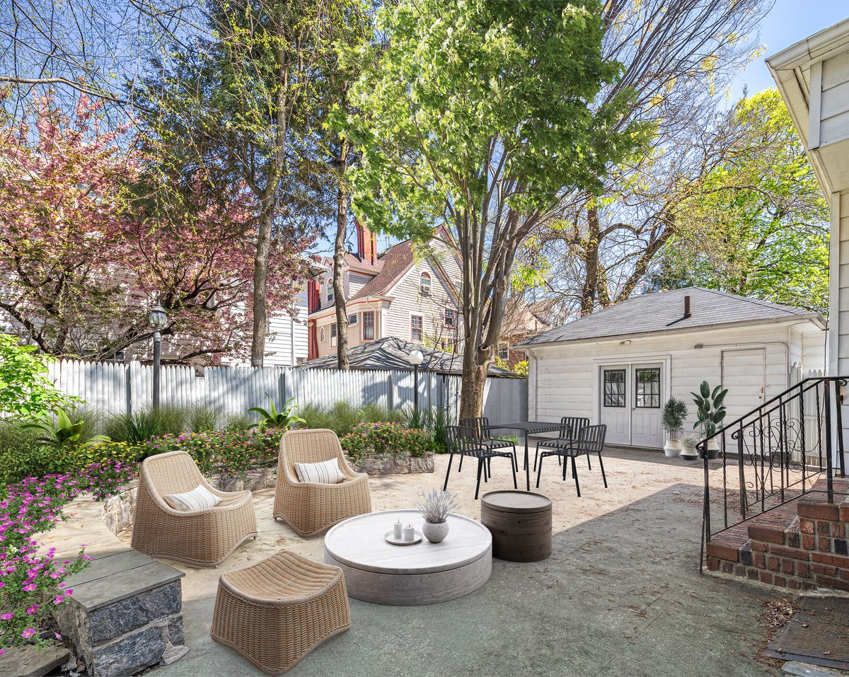A backyard with a tree, several plantings, a wooden fence, and two seating areas.