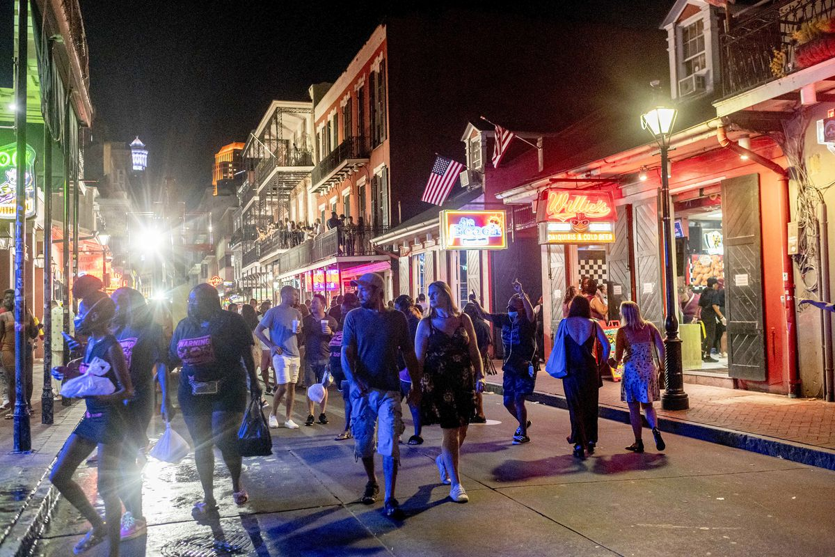 Crowds of people stroll down a lit-up nighttime street in New Orleans.