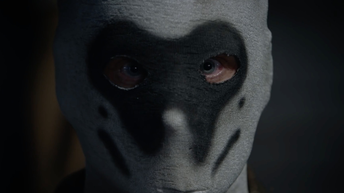 A close-up of a Rorschach-masked vigilante delivering an impassioned speech.