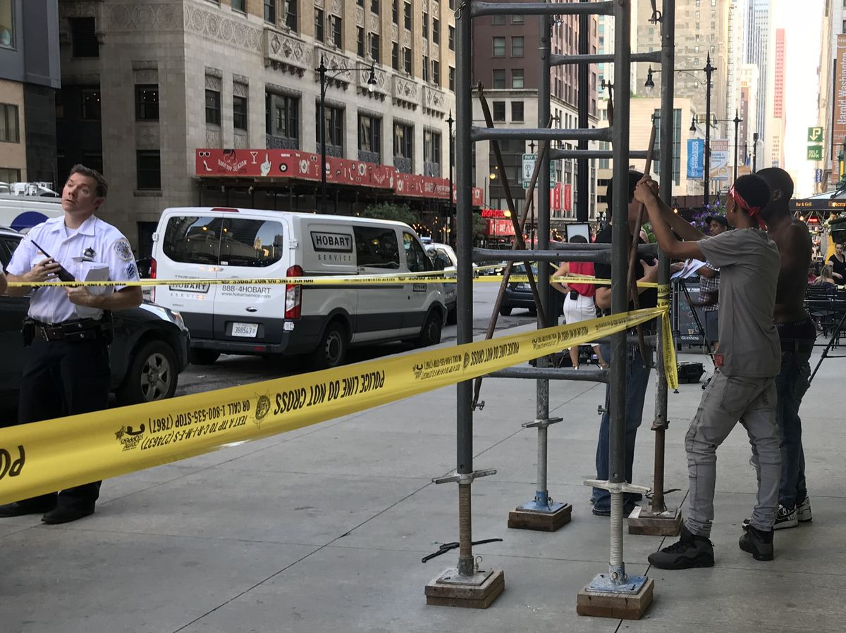 The brother and uncle of a teenage boy who was shot Friday wait near a crime scene in the Loop. | Matthew Hendrickson/Sun-Times