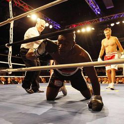 Evander Holyfield, left, gets up after a knockdown by former Massachusetts Gov. Mitt Romney during the Charity Vision Fight Night event in Salt Lake City, Friday, May 15, 2015.