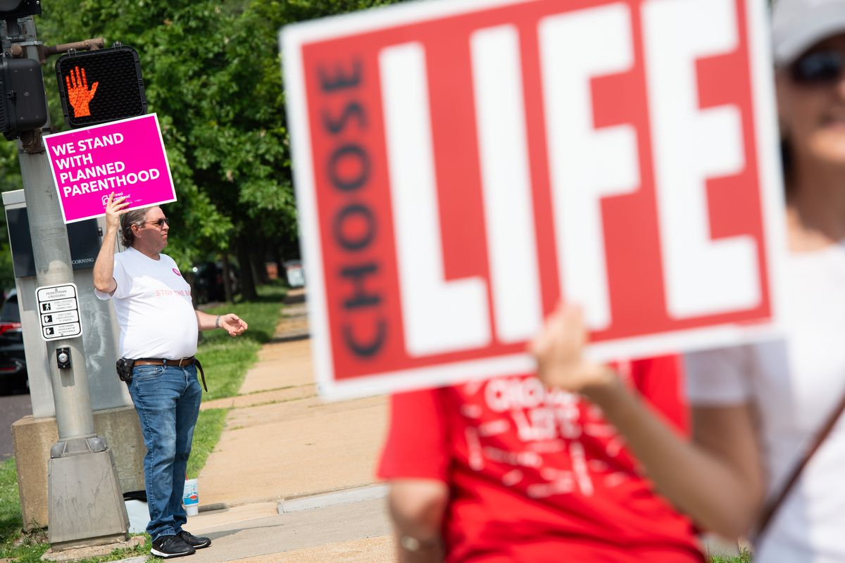 """A man holds a sign reading """"We stand with Planned Parenthood,"""" and another person holds a sign reading """"Choose life,"""" outside the Planned Parenthood Reproductive Health Services Center in St. Louis, Missouri, on May 31, 2019."""