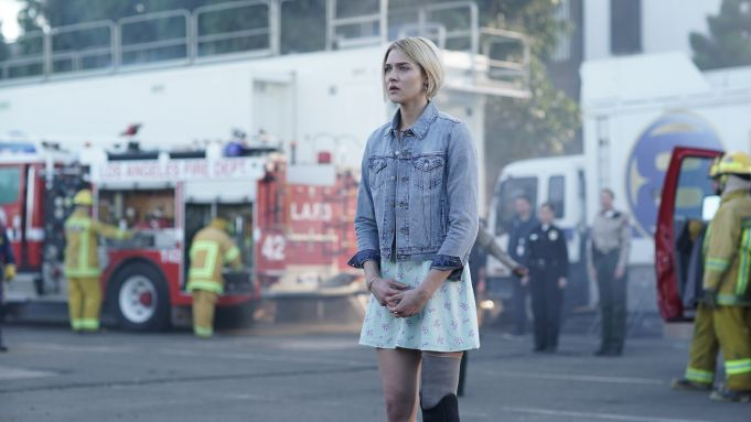 A young woman in a blue jean jacket and skirt stands with fire fighters and police officers in the background