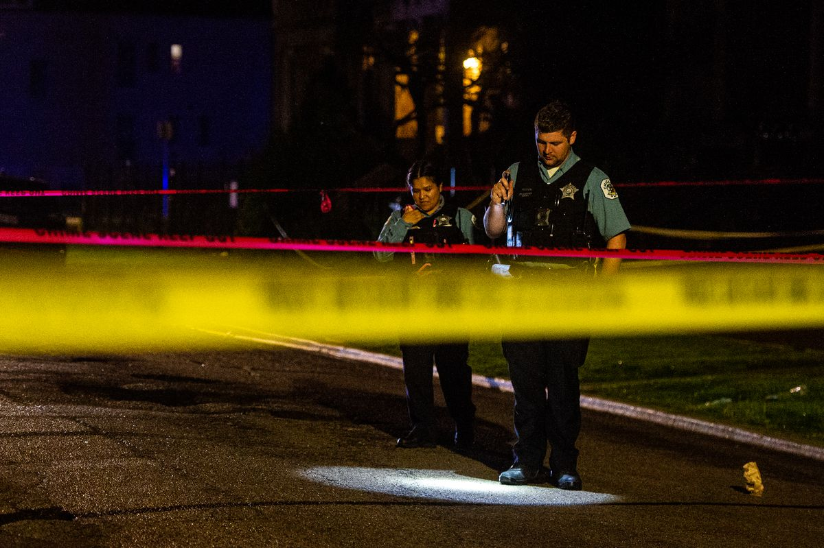 Chicago Police investigate the scene where two people were shot in the 1500 block of South Sawyer, Friday night in the Lawndale neighborhood.