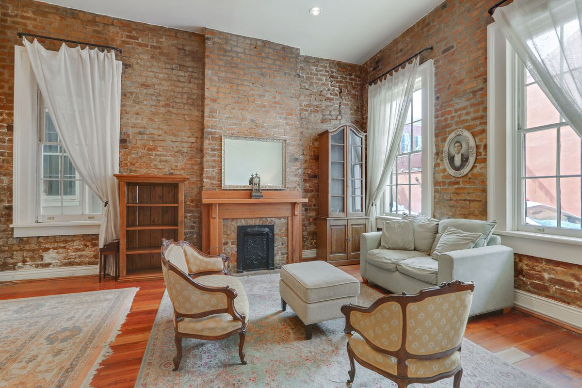 A furnished living room with brick walls, a fireplace, wood floors, and large windows.