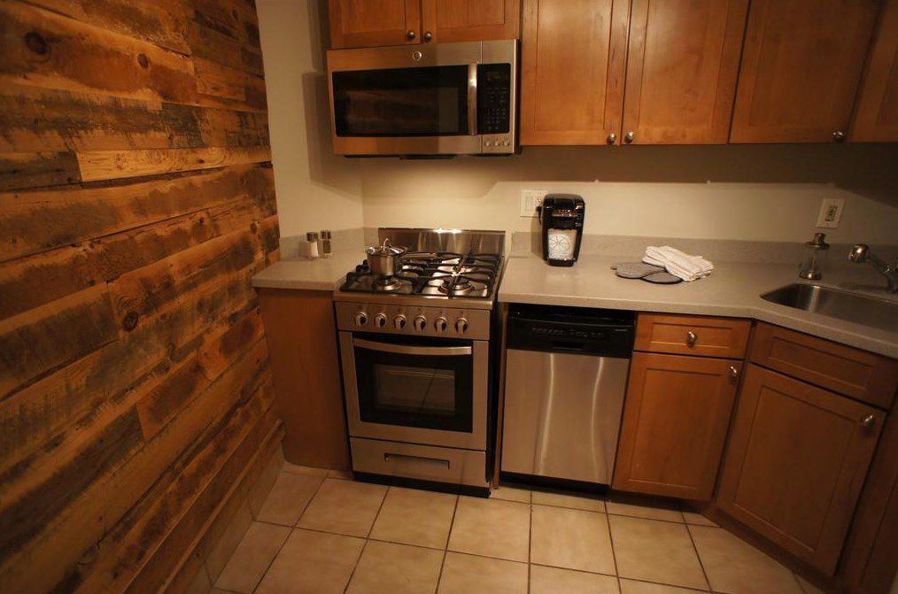 A small kitchen with a v-shaped counter next to a brick wall.