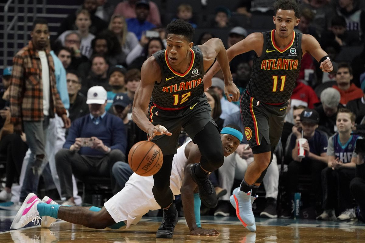 Atlanta Hawks forward De'Andre Hunter gets a loose ball from Charlotte Hornets guard Terry Rozier and heads up court in the first half at Spectrum Center.