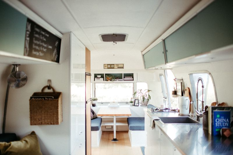 The interior of an Airstream travel trailer with eggshell blue cabinets, stainless steel countertops, and a dinette.