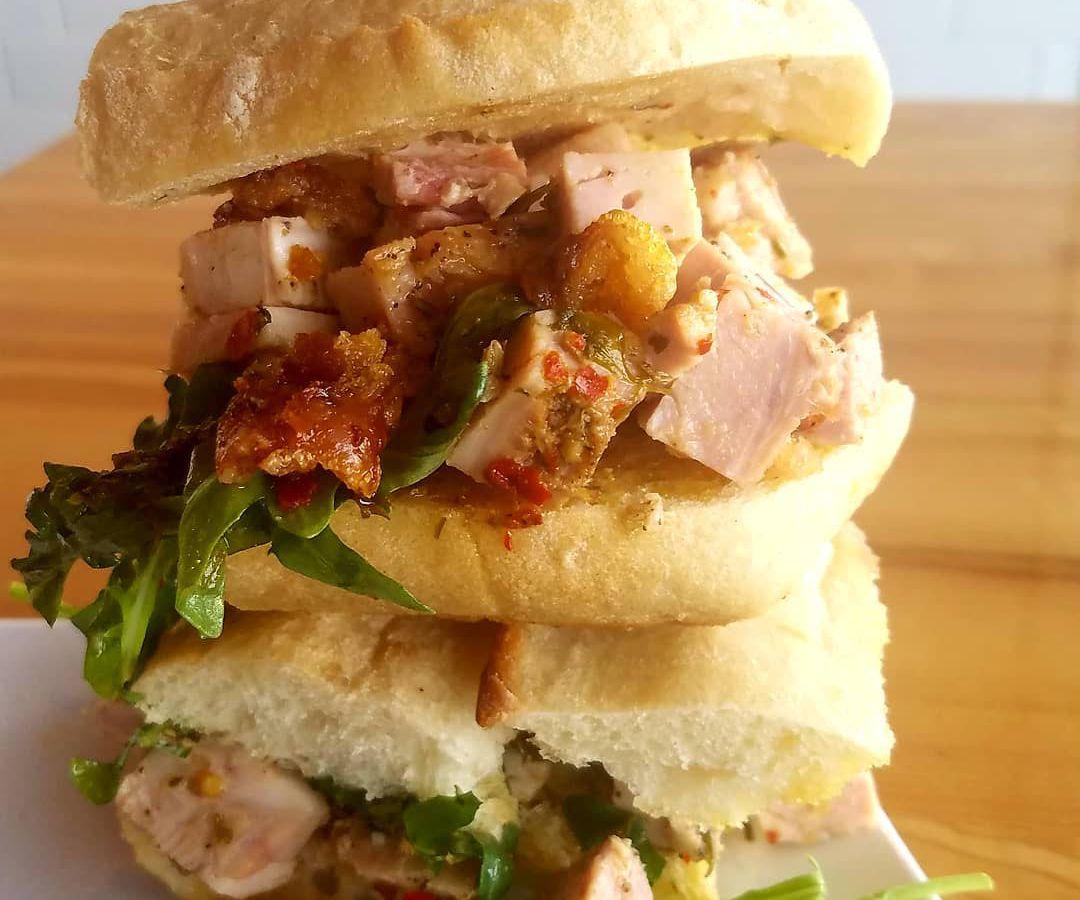 A porchetta sandwich cut in hhalf and stacked