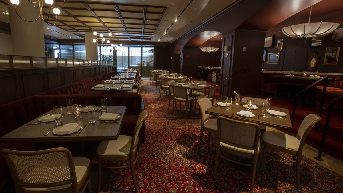 A restaurant's dining room with tons of dark booths, a red rug, and windows in the back.
