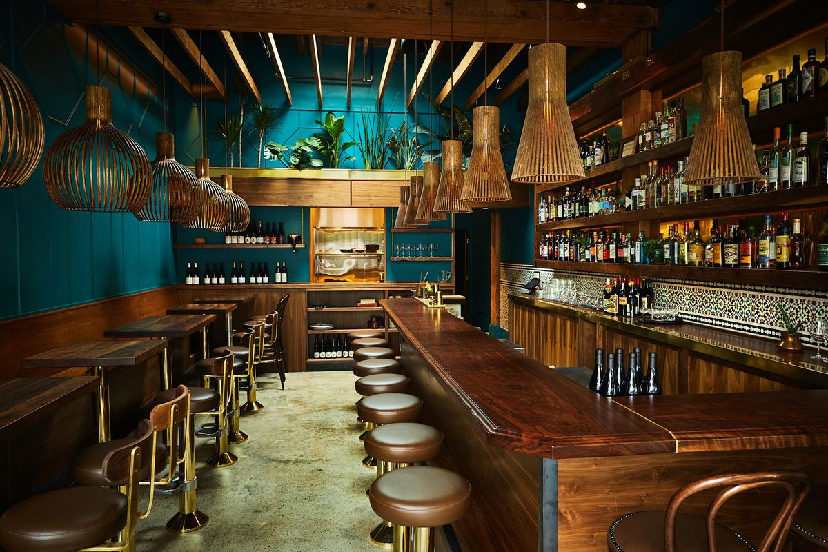 A view of Rupee Bar, with soft lighting, blue walls, and a dark wood bar.