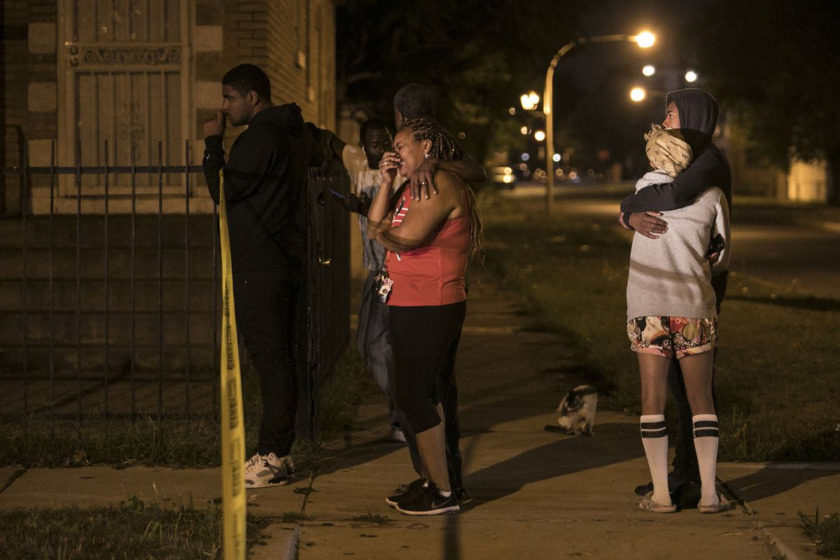 Family members and friends watch as Chicago Police investigate in the 6600 block of South Oakley, where a 28-year-old man was shot to death early Tuesday, Sept. 26, 2017. | Ashlee Rezin/Sun-Times