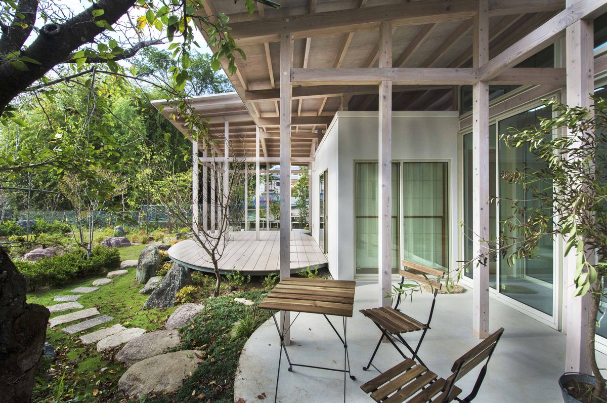 Small table and chairs on exterior patio surrounded by trees and shrubs.