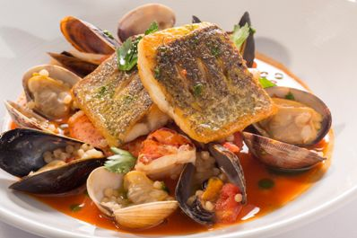 A seafood dishe with salmon, clams, mussels, and red sauce on a white plate.