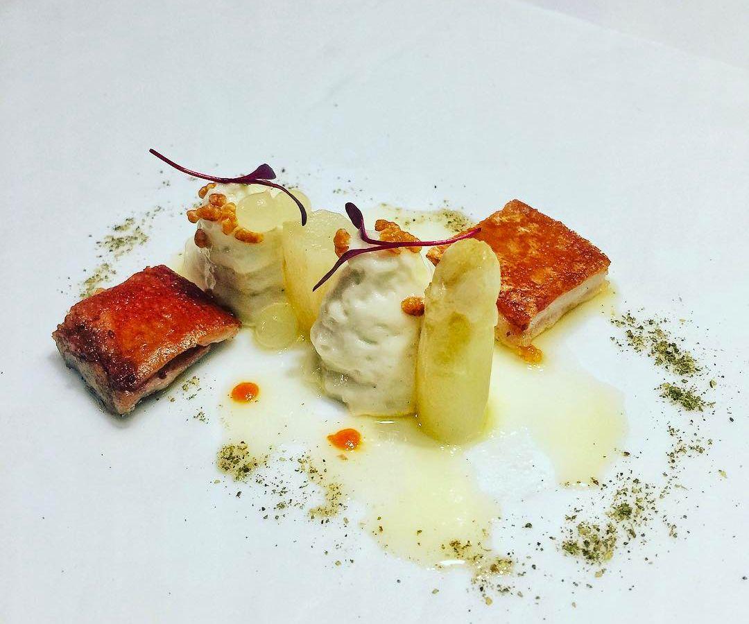 Cuadrados de cerdo crujiente dispuestos artísticamente en un plato blanco rígido junto a varios acentos de color crema y blanco en diferentes formas y texturas.
