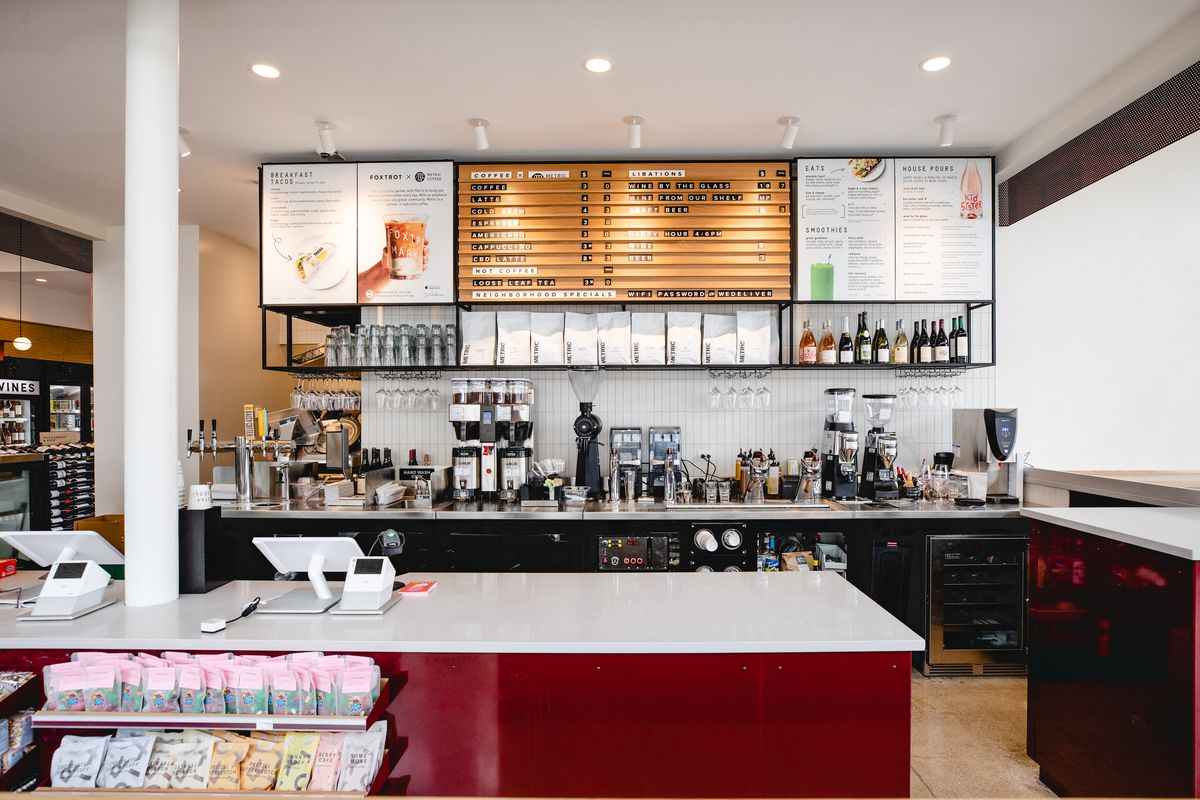 A red, white, and black espresso bar with a wooden sign listing menu options and prices