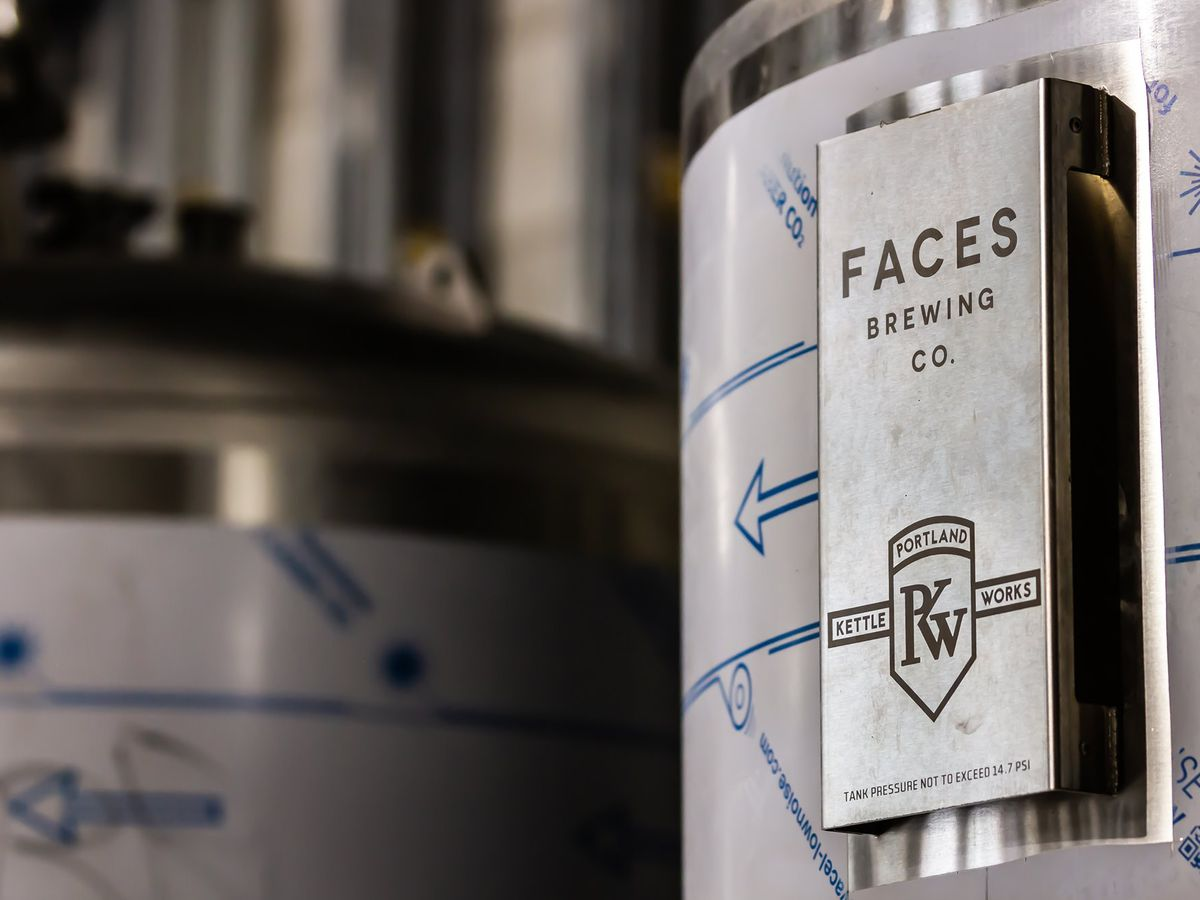 A silver fermentation tank displays the name of Faces Brewing Company, a forthcoming Malden brewery