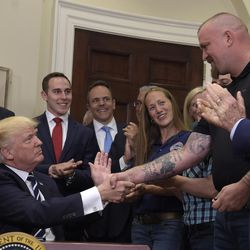 President Donald Trump shakes hands with Charles Robel after signing an executive in the Roosevelt Room of the White House in Washington, Thursday, June 15, 2017, during an event on Apprenticeship and Workforce of Tomorrow initiatives. He is joined by South Carolina governor Henry McMaster, left, and Commerce Secretary Wilbur Ross, right.