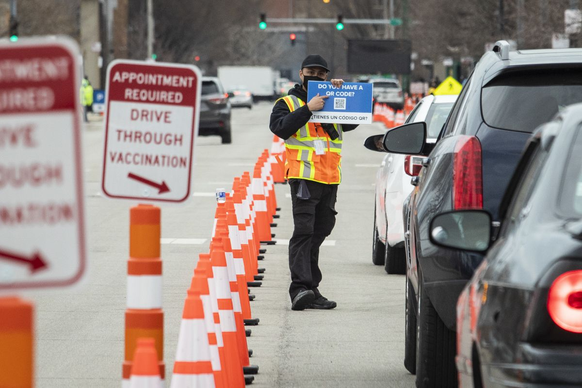 People approach to receive doses of a COVID-19 vaccine at the United Center's drive-thru vaccination site on Tuesday afternoon. More than 5 million shots have been given across Illinois.