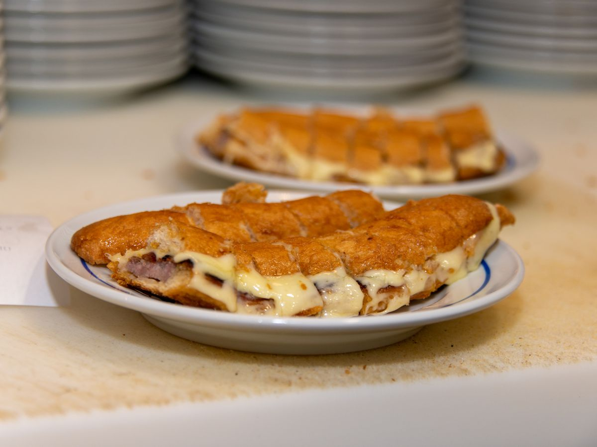 Several plates of cachorrinhos (hot dogs stuffed in chopped bread with cheese) sit on a kitchen counter