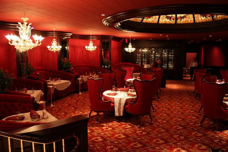 A dining room in red with chandeliers and red velvet booths
