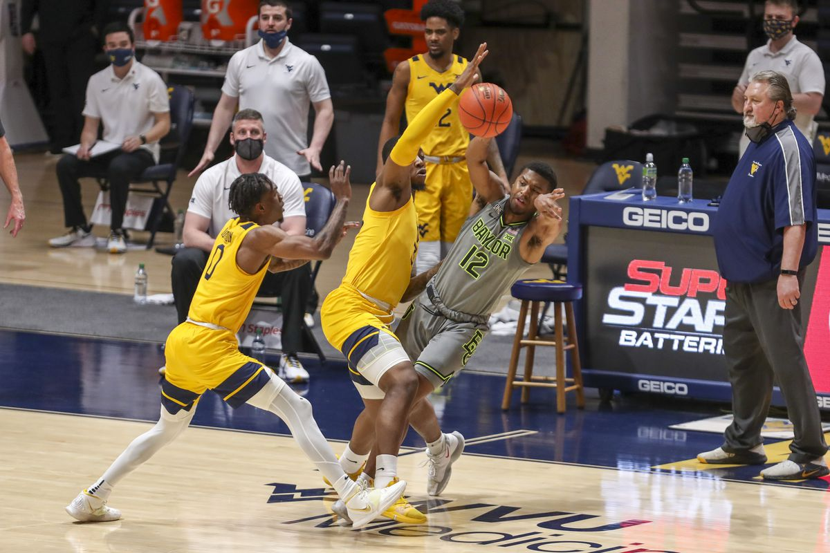 Baylor Bears guard Jared Butler passes the ball while being pressured by West Virginia Mountaineers forward Gabe Osabuohien and guard Kedrian Johnson during the first half at WVU Coliseum.