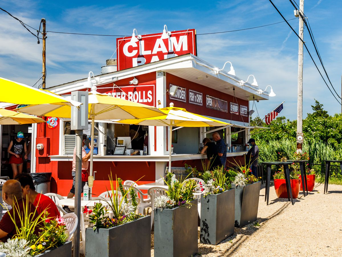 A red and white roadside clam shack with dark grey planters set up out front and tables and chairs under yellow umbrellas