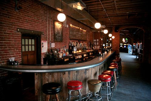 a curved bar with red and black stools